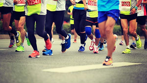 Photo of several people's legs while running in a 5K race.
