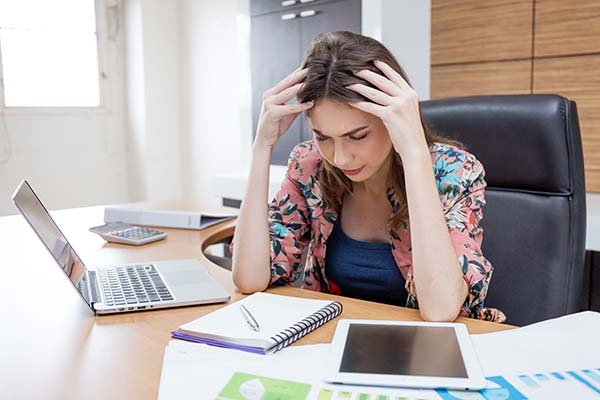 Photo of a woman looking stressed out and rubbing her head.
